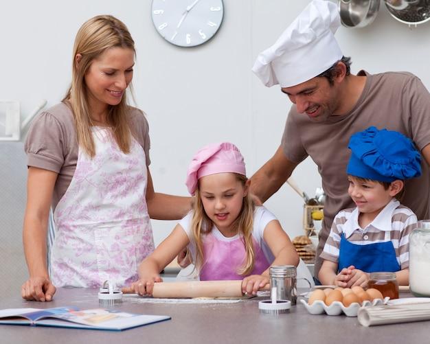 キッチンでベーキングをする子供たちを助ける親