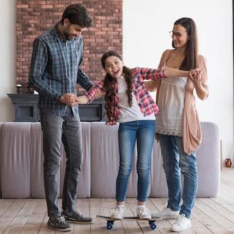 スケートボードに乗る女の子を助ける親