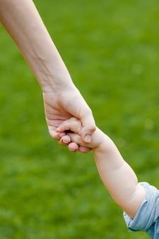 Родители держатся за руки ребенка
