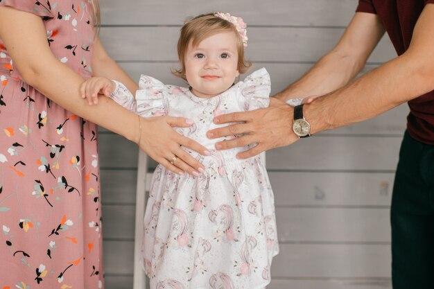 両親は小さな笑顔の子供を手に持っています。