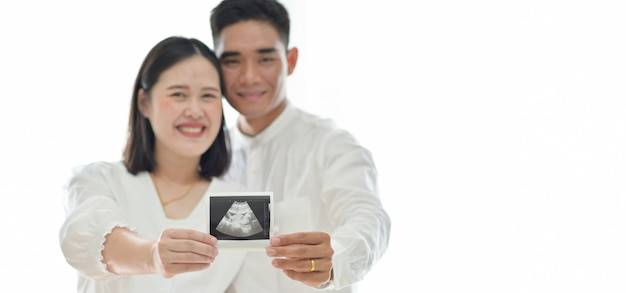 Parents hold ultrasound results of the fetus. Premium Photo