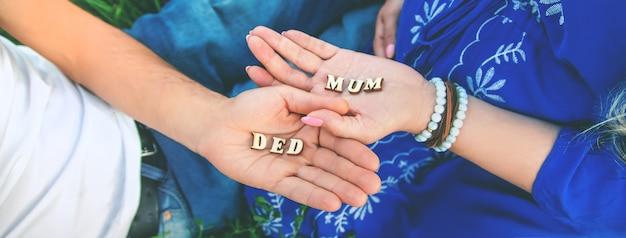 Родители держат в руках буквы, образующие слова мамы и папы