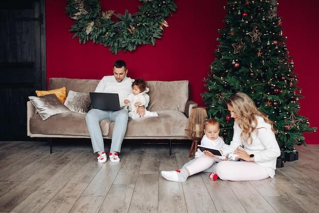 Genitori che tengono i loro figli e guardano gli schermi dei loro dispositivi elettrici vicino all'albero di natale