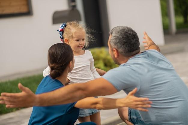Родители обнимают девушку. любящие родители обнимают свою прекрасную маленькую девочку, возвращаясь с работы
