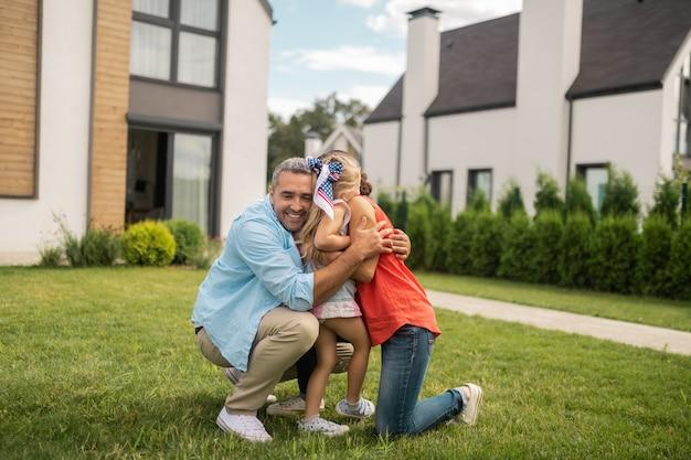 女の子を抱き締める両親。家の近くの外で小さな素敵な娘を抱き締める両親