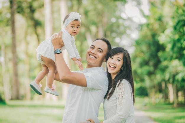 公園で赤ん坊の娘と歩いて白い服を着た両親