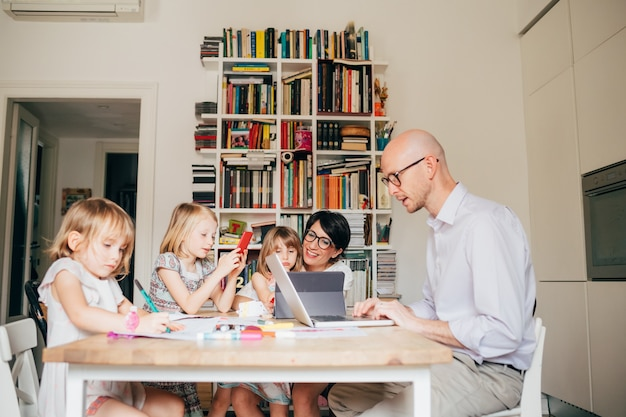 Parents indoor sitting table homeschooling with three female children