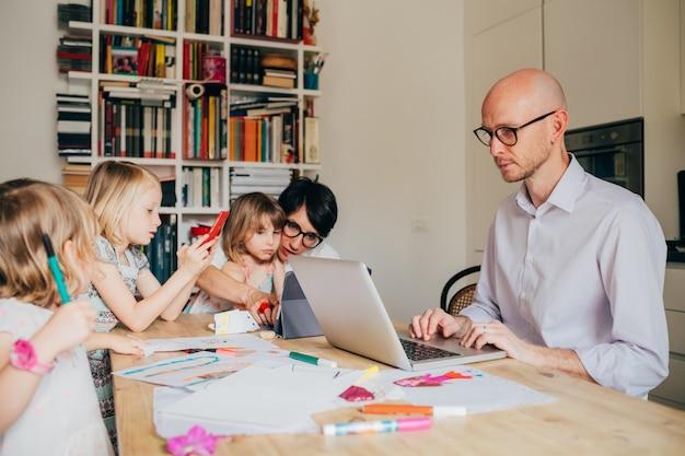 세 여자 아이와 부모 실내 앉아 테이블 홈 스쿨링