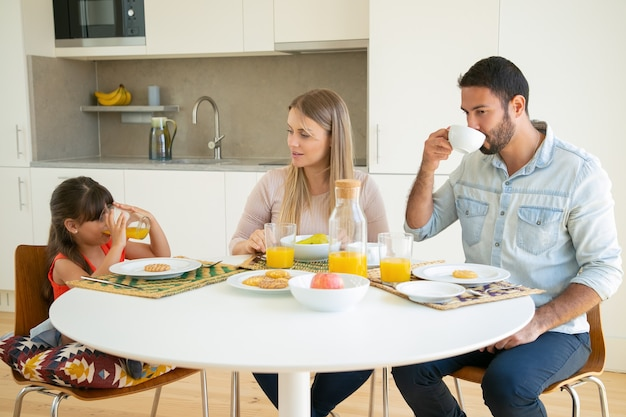 Parents and kid enjoying breakfast together, drinking coffee and orange juice, sitting at dining table with fruits and cookies and talking.