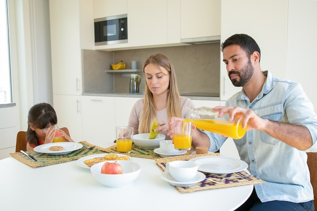 Parents and kid sitting at dining table with dish, fruit and cookies, pouring and drinking fresh orange juice.
