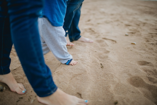 Parents and kid stepping in the sand