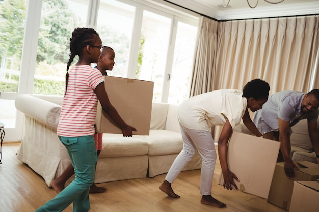 Parents and kids carrying cardboard boxes in living room