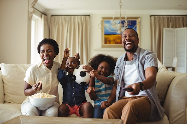 Parents and kids having fun while watching television in living room