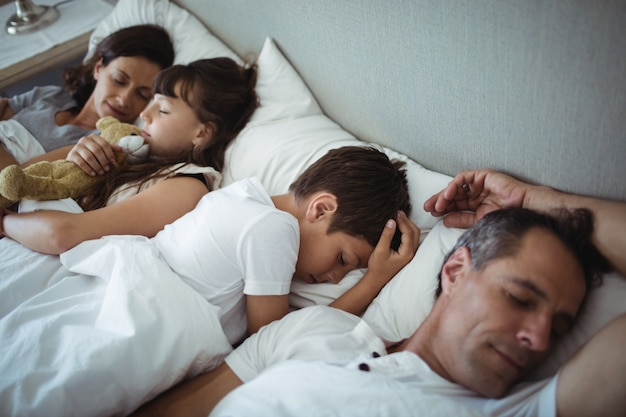 Parents and kids sleeping on bed