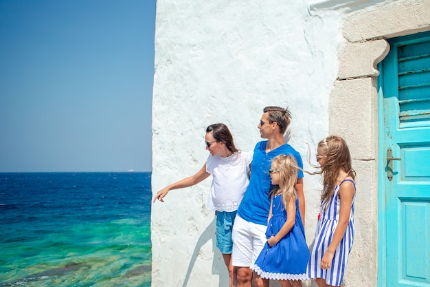 Parents and kids at street of typical greek traditional village on mykonos island, in greece