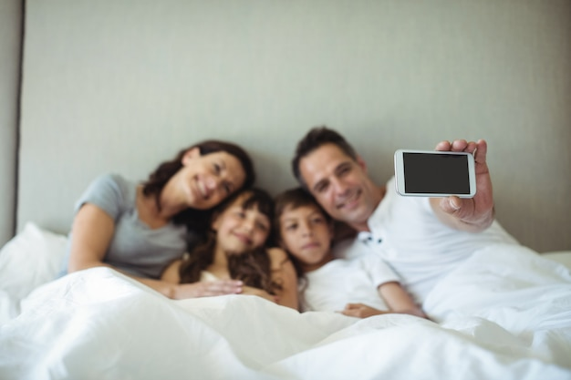 Parents and kids taking a selfie on bed