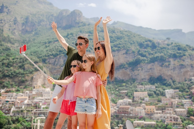 Parents and kids taking selfie photo onpositano town in itali on amalfi coast