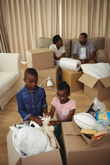 Parents and kids unboxing cardboard boxes in living room