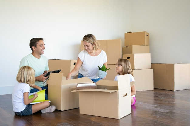 Parents and kids unpacking things in new apartment, sitting on floor and taking objects from box