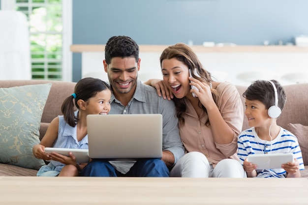 Parents and kids using laptop and digital tablet in living room