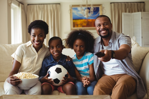 Parents and kids watching television in living room