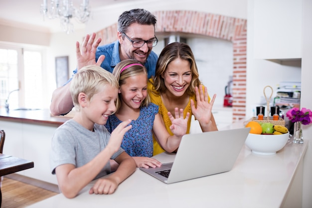 Parents and kids waving hands while using laptop for video chat