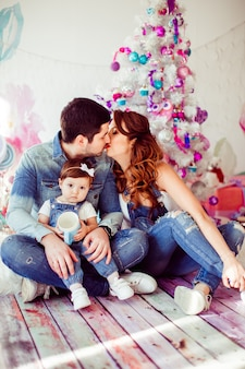 Parents kiss sitting with their little daughter before bright christmas tree
