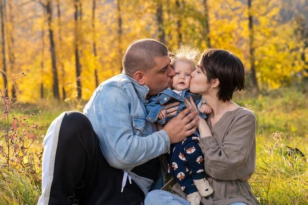 Родители целуют годовалую дочь в обе стороны щеки