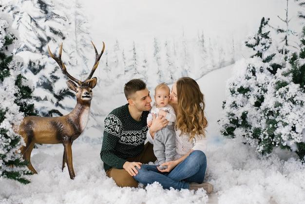 Родители целуют сына и сидят на искусственном снегу в фотозоне на рождество и новый год в зимнем лесу с оленем