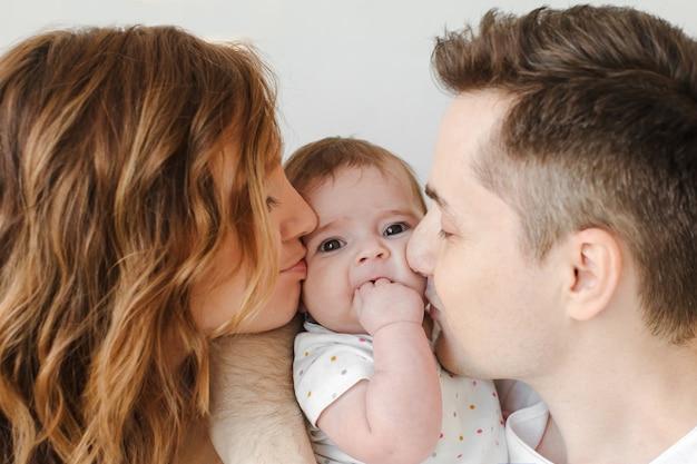 頬に赤ちゃんをキスする親