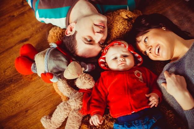 Parents lie around little girl in red jacket