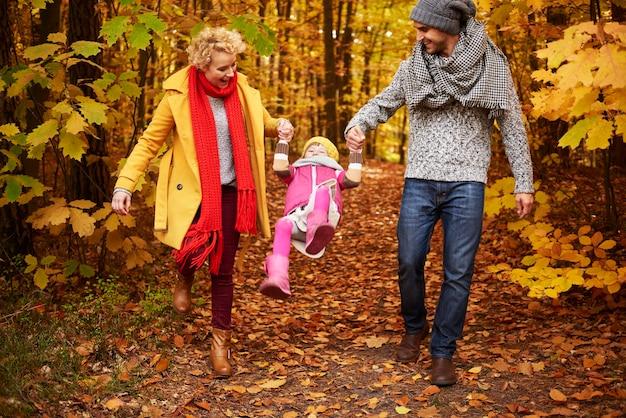 Родители поднимают дочь в воздух