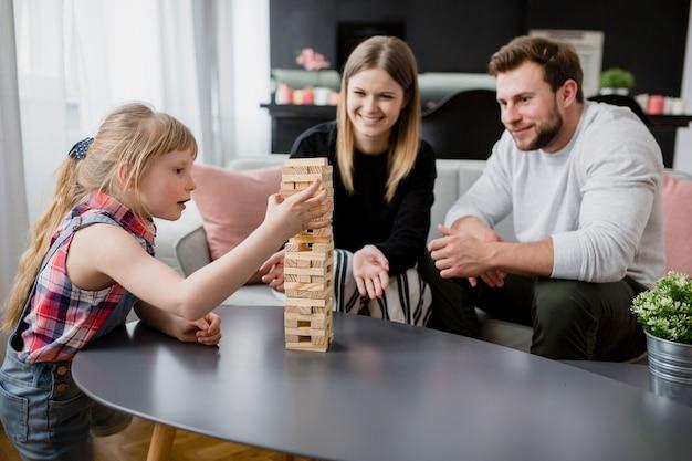 Родители смотрят на дочери, удаляющие блоки