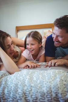 両親は娘とベッドの上に横たわって、フォトアルバムを見て