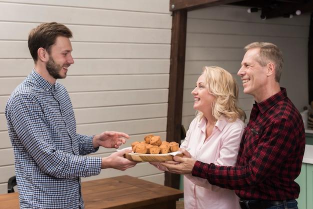 Родители предлагают сыну тарелку кексов