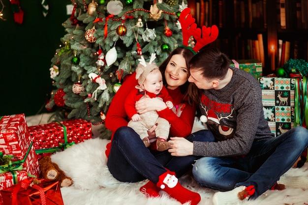 Родители играют с маленькой дочкой в шляпе оленя, держа ее на руках и сидят перед рождественской елкой