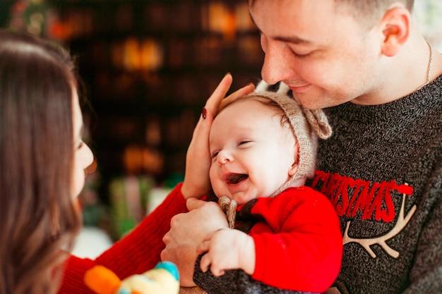 Родители играют с маленькой дочкой в шляпе оленя, держа ее на руках и стоят перед рождественской елкой