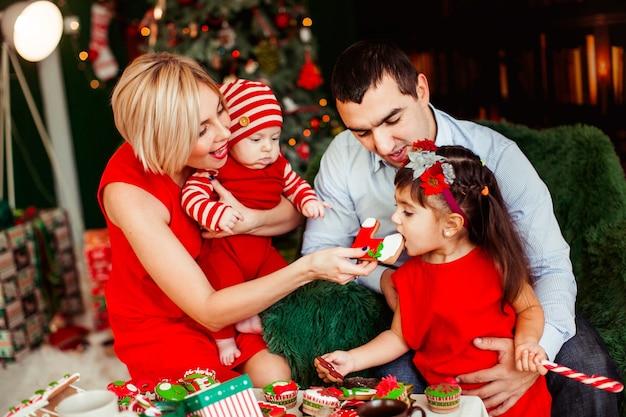 Родители играют со своими двумя детьми за столом перед зеленой елкой