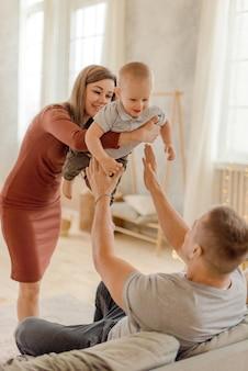Родители играют с сыном в спальне