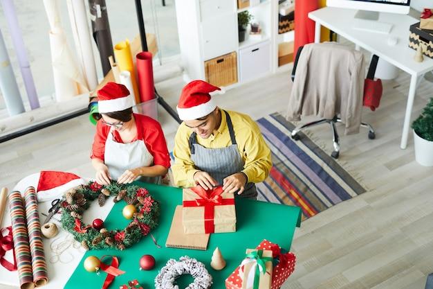 Genitori che preparano addobbi natalizi e confezionano regali