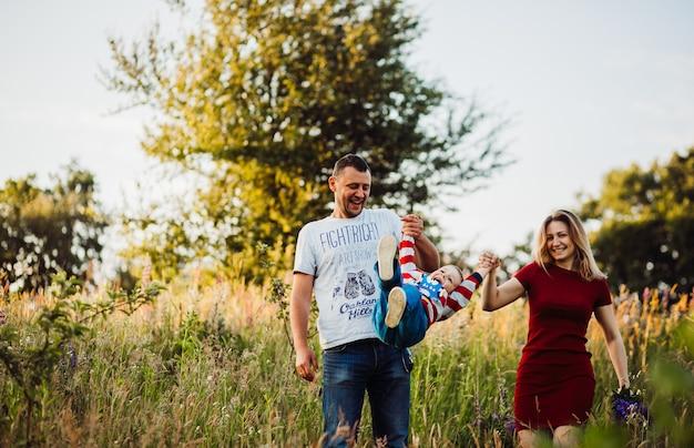 I genitori allevano il loro figlio camminando con lui sul campo