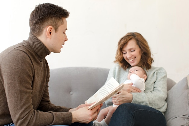 Parents reading book to baby in living room