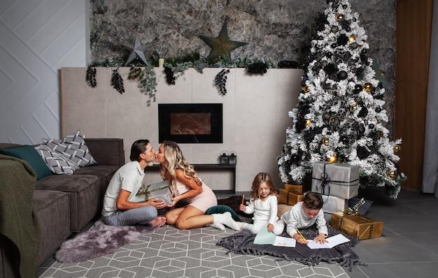 両親がリラックスして家のプレゼントギフト一緒に絵を描いて遊んでいる子供たちクリスマスを祝う家族