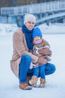 両親は娘をそりに乗せて、橋を背景に凍った湖を楽しんでいます