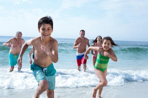 Parents running behind children at beach