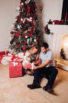 Parents sitting on floor with child near christmas tree.