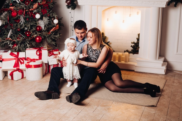 Parents sitting on floor with cute child in living room. apartment decorated with christmas tree, candles, lamps, white gift boxes with red bows. cute little girl wearing in white dress.