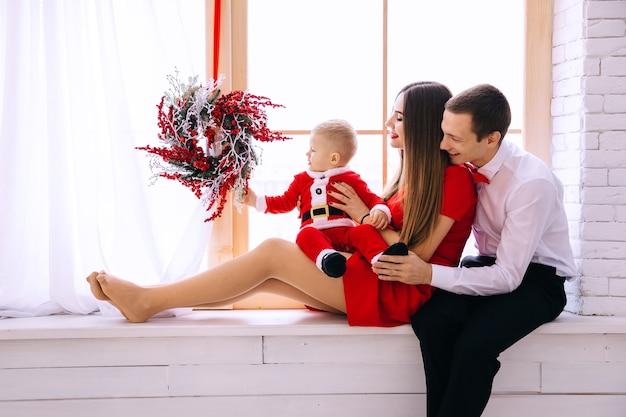 窓辺に座って赤ちゃんを抱いている両親。窓はクリスマスリースで飾られています。