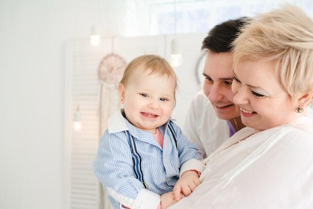 自分の赤ちゃんを見ながら笑顔の両親