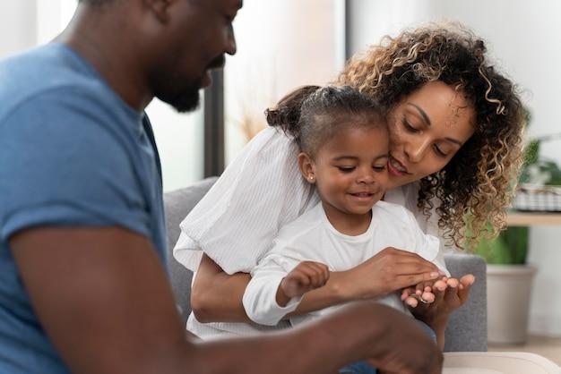 I genitori trascorrono del tempo con la loro piccola figlia a casa